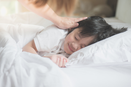Photo pour Cute Asian child sleeping on white bed with mother care - image libre de droit