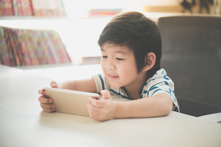 Photo for Happy Asian child using mobile phone on white table - Royalty Free Image