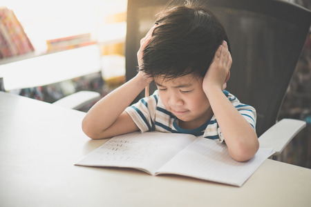 Foto de Unhappy Asian child working on hard homework at home alone - Imagen libre de derechos