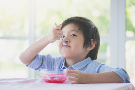 Photo for Happy little asian child eating Shaved ice at home - Royalty Free Image
