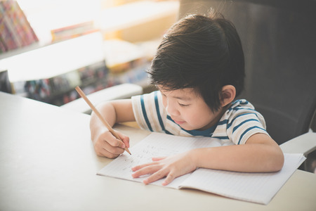 Foto de Little Asian child  using a pencil to write on notebook at the desk - Imagen libre de derechos