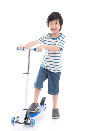 Photo pour Cute Asian boy riding a scooter on white background isolated - image libre de droit