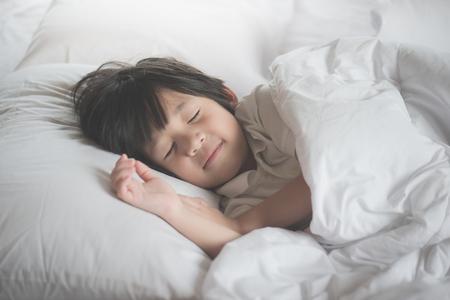 Photo pour Cute asian child sleeping on white bed - image libre de droit