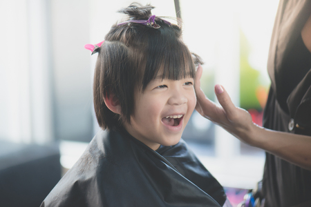 Photo for Cute Asian boy getting haircut at hairdresser salon - Royalty Free Image