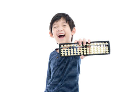 Foto de Cute Asian child holding Soroban abacus on white background isolated - Imagen libre de derechos