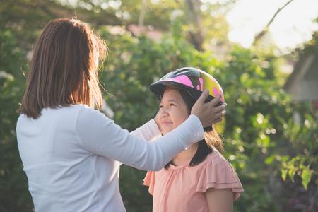 Foto de Asian mother wears a bicycle helmet to her daughter - Imagen libre de derechos