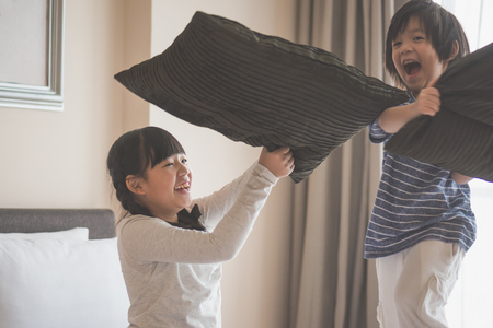 Foto de Happy Asian child ren having Pillow Fight in Hotel Room - Imagen libre de derechos