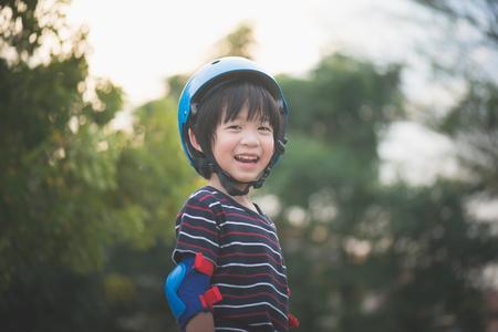 Photo pour Portrait of happy Boy in blue helmet standing with nature background - image libre de droit