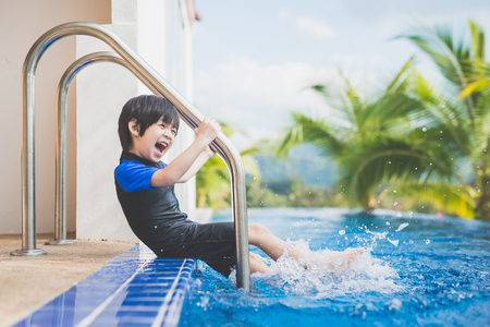 Photo for Asian child splashing around in the pool - Royalty Free Image