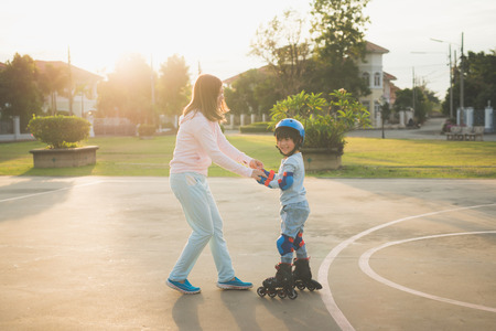 Foto de Asian mother helping her son to playing roller skate in the park - Imagen libre de derechos