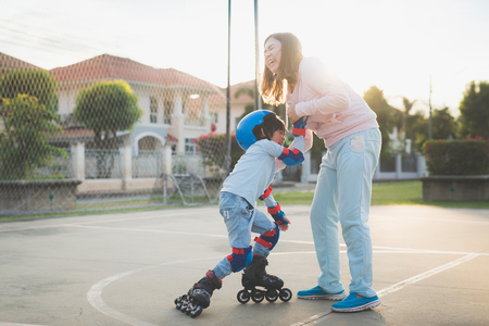 Photo pour Asian mother helping her son to playing roller skate in the park - image libre de droit