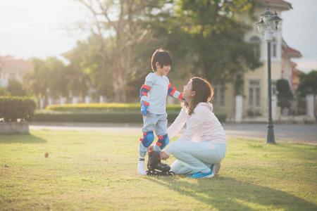 Foto de Asian mother helping her son putting his roller skates on enjoying time together in the park - Imagen libre de derechos