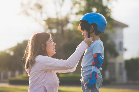 Foto de Asian mother helping her son wears blue helmet on enjoying time together in the park - Imagen libre de derechos