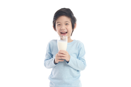 Photo pour Asian child drinking milk from a glass on white background isolated - image libre de droit