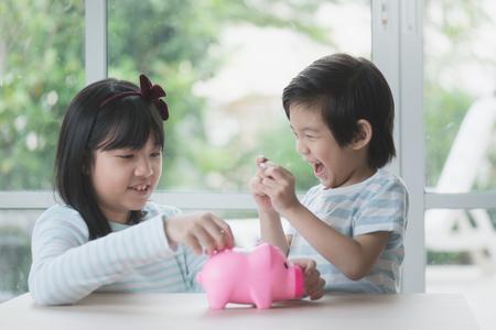 Foto de Cute Asian child putting a coin into a piggy bank - Imagen libre de derechos