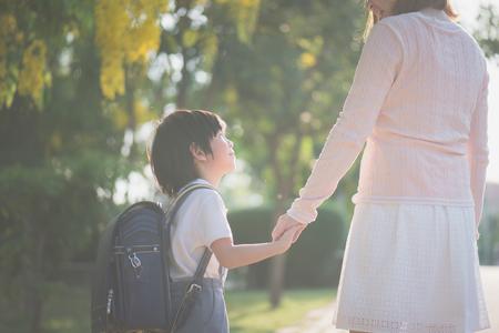 Foto de Asian mother holding hand of little son with backpack outdoors, back to school - Imagen libre de derechos