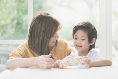 Photo pour Asian mother and her son playing wooden car toy together - image libre de droit