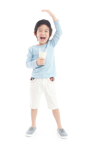 Foto de Asian child drinking milk from a glass and measuring himself  on white background isolated - Imagen libre de derechos