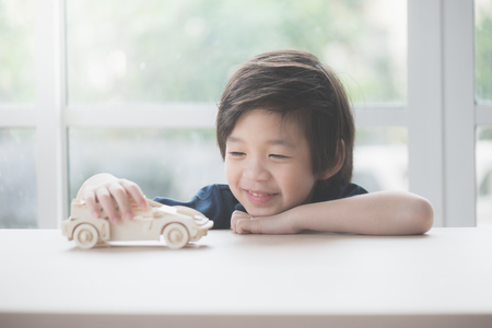 Foto de Cute Asian child playing wooden model car on a table - Imagen libre de derechos