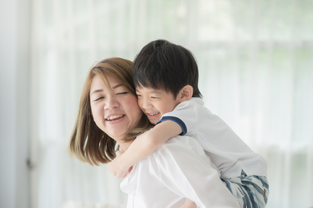 Foto de Asian child on a piggy back ride with his mother at home - Imagen libre de derechos