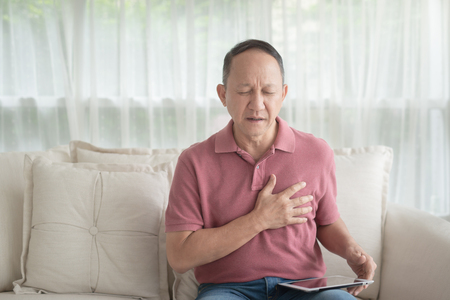Photo pour Asian old man with chest pain suffering from heart attack in home - image libre de droit