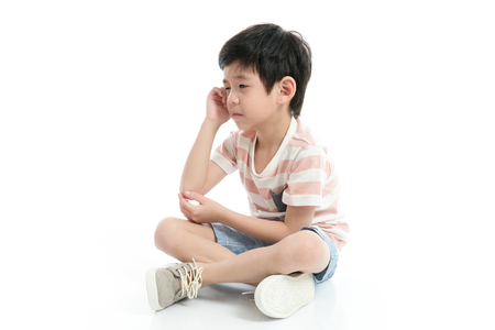 Photo pour Close up of sad Asian boy sitting on white background isolated - image libre de droit