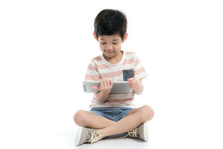 Photo pour Cute Asian child with a tablet sitting on white background isolated - image libre de droit