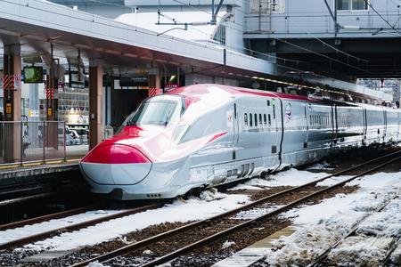 Foto de JAN 29, 2019 AKITA, JAPAN : Komachi Super Express Shinkansen E6 series on a snowy train station in winter - Imagen libre de derechos