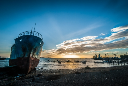 Foto de Abandoned and ruined ship in the harbor of Makassar, Indonesia at sunset - Imagen libre de derechos