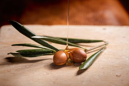 Photo pour Argan oil, used for cosmetics, puring over two argan seeds on a stone table. - image libre de droit