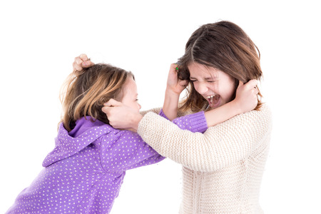 Photo pour Young girls fighting, pulling hairs isolated in white - image libre de droit