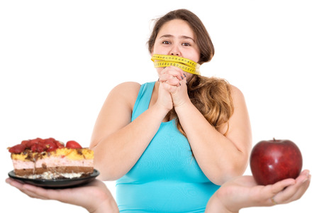 Photo pour Beautiful large girl gagged with measuring tape lokking at a cake and an apple isolated in white - image libre de droit