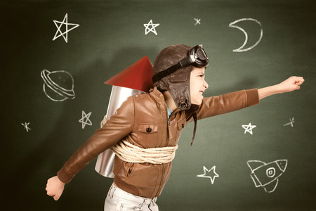 Photo pour Young boy with home made rocket ready for adventure in classroom - image libre de droit