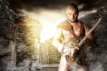 Foto de Gladiator or warrior posing with shield and sword outdoors ready for battle - Imagen libre de derechos