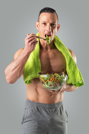 Photo for Powerful athletic man with great physique eating a healthy salad. - Royalty Free Image