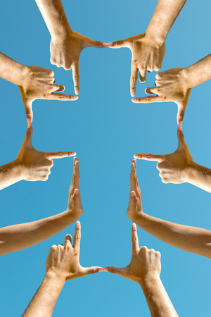 Photo pour Hands forming a cross against the blue sky - image libre de droit