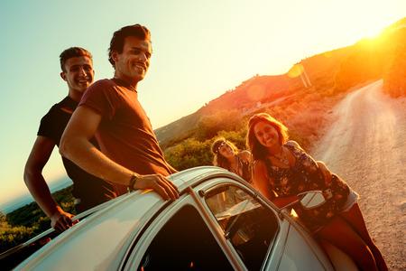 Foto de Group of happy people in a car at sunset in summer. - Imagen libre de derechos