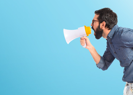 Photo for Young hipster man shouting by megaphone - Royalty Free Image