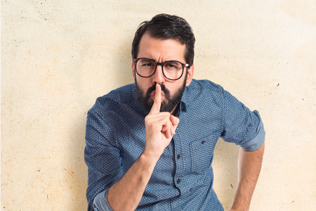 Photo pour Young hipster man making silence gesture - image libre de droit