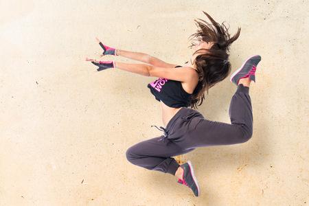 Foto de Teenager girl jumping in hip hop style - Imagen libre de derechos