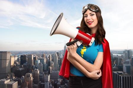 Foto de Pretty superhero girl shouting by megaphone with the city in the background - Imagen libre de derechos