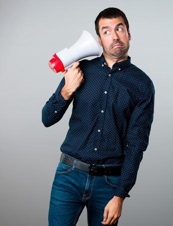 Photo pour Handsome man holding a megaphone on grey background - image libre de droit