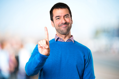 Photo for Handsome young man counting one on unfocused background - Royalty Free Image