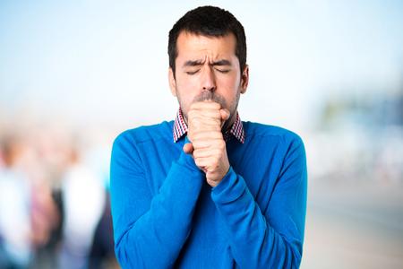Foto de Handsome young man coughing a lot on unfocused background - Imagen libre de derechos