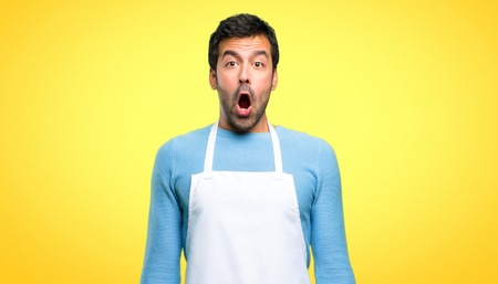 Photo pour Man wearing an apron with surprise and shocked facial expression. Gaping because have just surprised with a gift on yellow background - image libre de droit