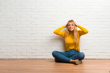 Photo pour Young girl sitting on the floor takes hands on head because has migraine - image libre de droit