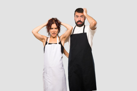 Photo pour Couple of cooks takes hands on head because has migraine on grey background - image libre de droit
