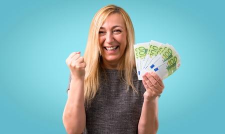 Photo pour Middle-age blonde woman happy because has won a lot of money on colorful background - image libre de droit