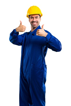 Photo pour Young workman with helmet giving a thumbs up gesture and smiling because has had success on isolated white background - image libre de droit