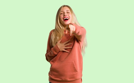Photo pour Young girl pointing with finger at someone and laughing a lot on green background - image libre de droit